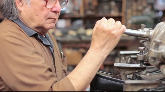 stockvideo's en b-roll-footage met ms shoemaker repairing a shoe in his shop / santa monica, california, united states - breedbeeldformaat