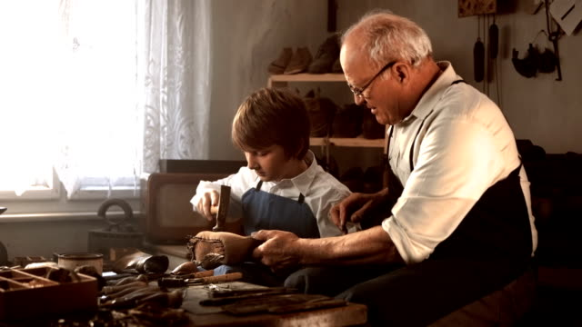 hd dolly: shoemaker teaching young apprentice - craftsman stock videos and b-roll footage