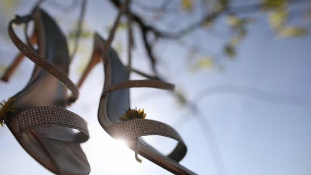 stockvideo's en b-roll-footage met schoenen opknoping op een boom in de achtertuin - schommelen bungelen