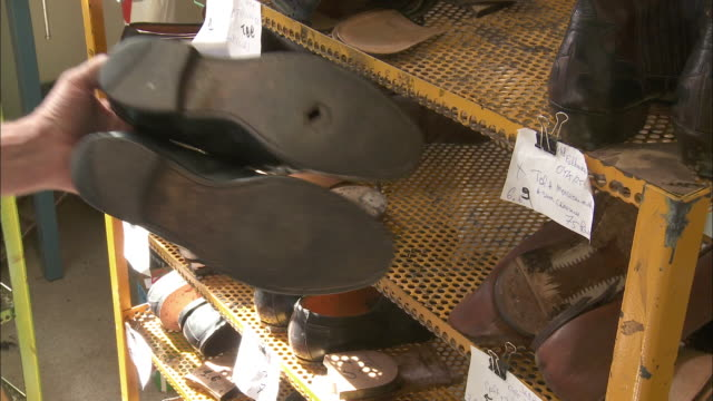 cu shoes in rack, man's hand showing pair with hole / brussels, belgium - hole stock videos & royalty-free footage