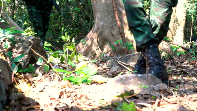 shoes of group of fully Equipped and Armed Soldier appear form are patrolling in tropical forest