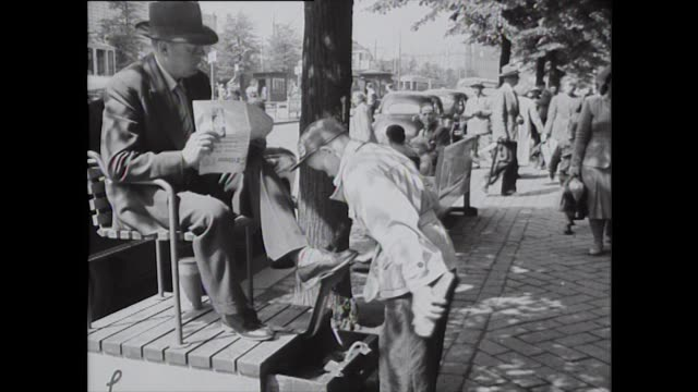 a shoeshine boy shines a man's shoes while he reads the paper in helsinki during the 1952 summer olympic games - summer olympic games stock videos and b-roll footage