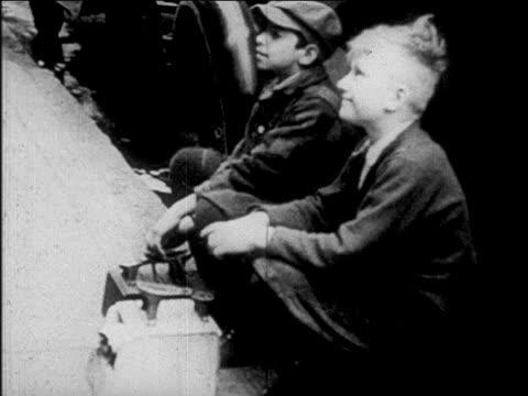 b/w 1927 2 shoeshine boys sitting looking up listening / newsreel - 1927年点の映像素材/bロール