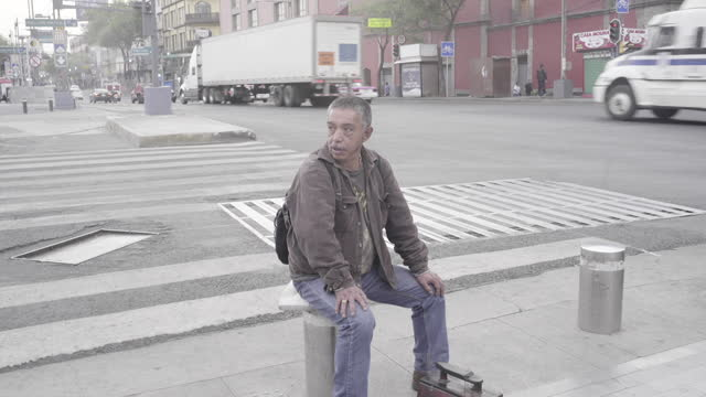 shoeshiner sits down on the corner of eje central street, nearby palacio de bellas artes museum and metro station. traffic and people passing by. - trådbuss bildbanksvideor och videomaterial från bakom kulisserna