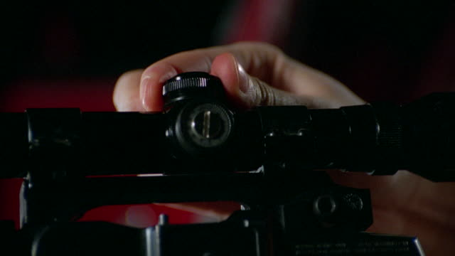 vidéos et rushes de a shooter adjusts his rifle scope and puts his finger on the trigger. - fusil