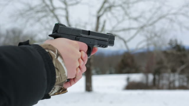 a shooter raises a smith & wesson m&p 9mm into the frame and fires 4 shots. - pistolenschießen stock-videos und b-roll-filmmaterial