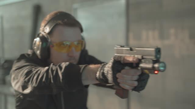 shooting a glock. mysterious man training shooting skills - rifle stock videos & royalty-free footage