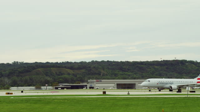 Shooting across several runways at a small airport; a commercial passenger jet crosses in background after landing.