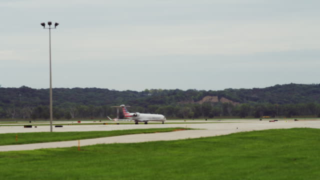 Shooting across several runways at a small airport; a small commercial jet taxis to end of runway prior to take-off.