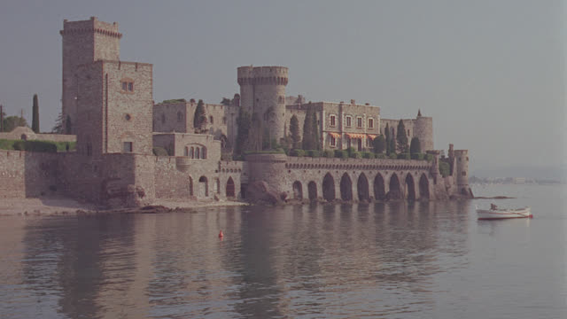 foreign: bldg. castle shooting across water to a castle on rock out mid distance. man in canoe enters from right and moves to left - mid distance stock videos & royalty-free footage