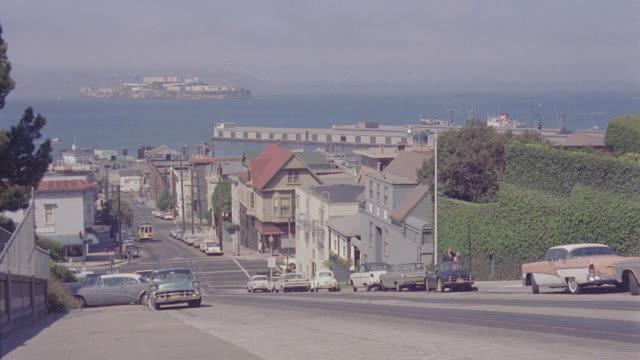 vídeos de stock e filmes b-roll de shooting down russian hill, hyde street, san francisco; san francisco bay & alcatraz visible; cable car uphill to camera - cable