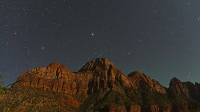 shooting stars shoot past constellations above zion national park. - ザイオン国立公園点の映像素材/bロール