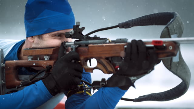 slo mo shooting the biathlon rifle in prone position - winter sport stock videos and b-roll footage