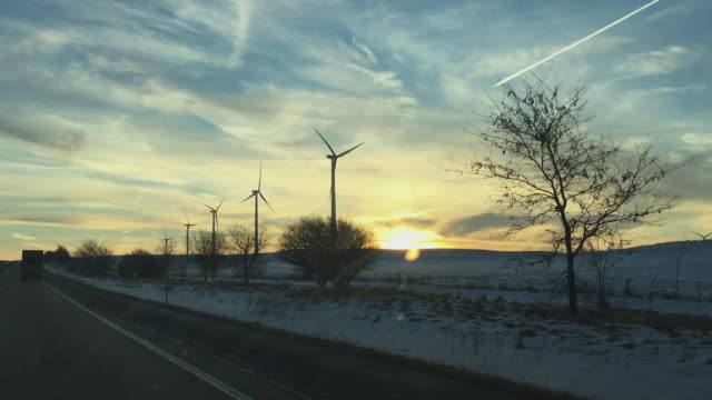 Shooting through the windshield of a car driving down the highway as the sun rises over a rural winter landscape featuring many air turbine windmills producing clean energy