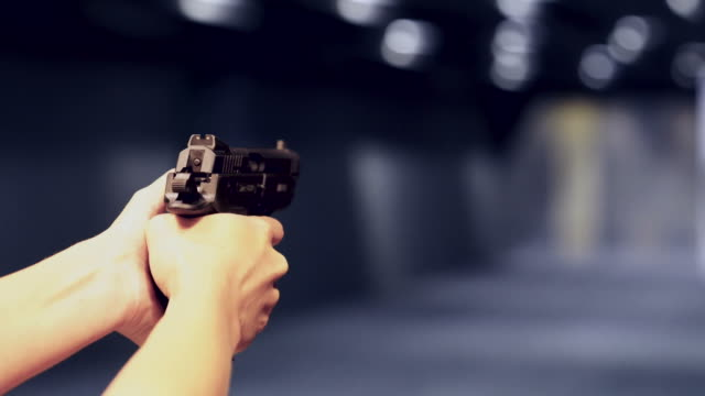 shooting with gun at target in shooting range - handgun stock videos and b-roll footage