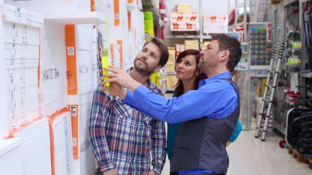 A shop assistant advises customers in a hardware store