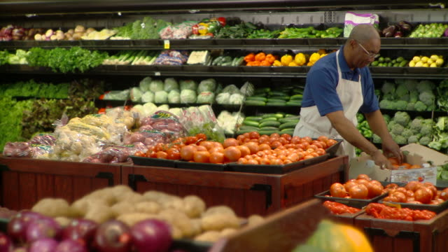 stockvideo's en b-roll-footage met ms pan shop assistant arranging tomatoes in greengrocer's shop, richmond,  virginia, usa - supermarkt