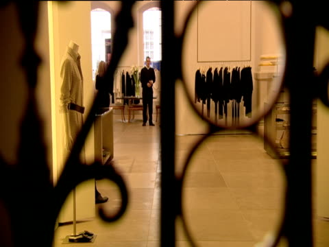 shop assistant carries clothes through minimalist designer boutique london - effigy stock videos & royalty-free footage