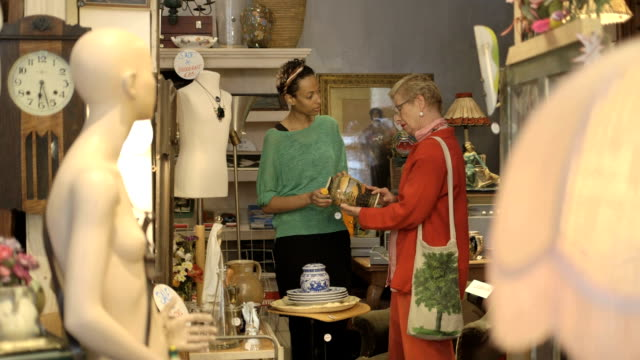 Shop assistant helps senior woman in antiques store