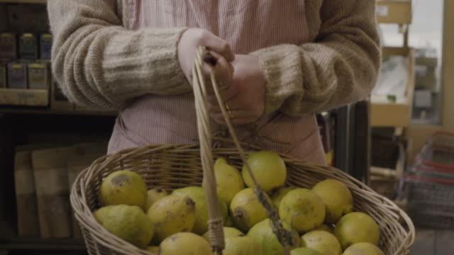 CU of shop assistant holding basket with organic lemons in farm shop.