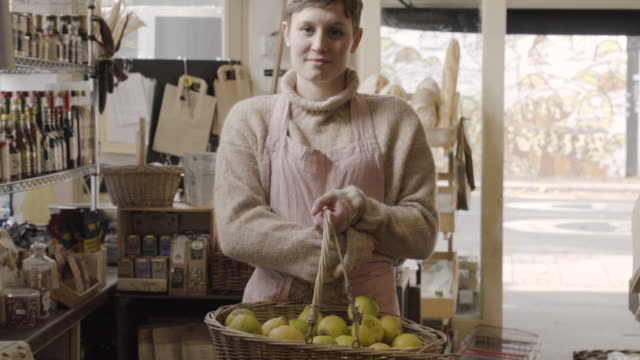 shop assistant holds basket with organic lemons in organic food store. - basket stock videos and b-roll footage
