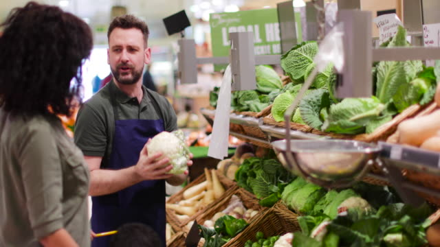 shop assistant in grocery store helping shoppers - greengrocer's shop stock videos & royalty-free footage