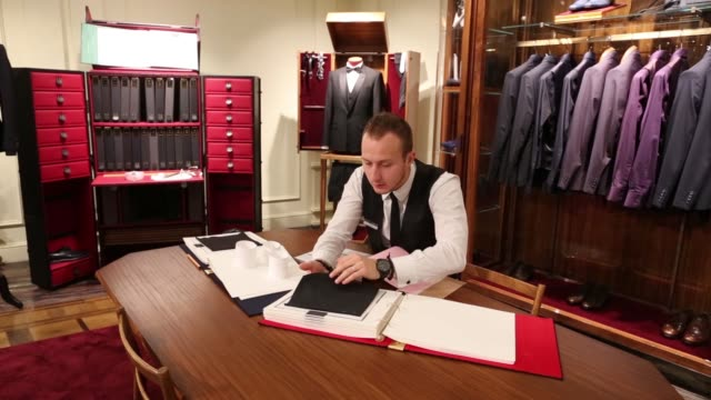 A shop assistant organising mens clothing in a Dolce Gabbana Boutique on Tretyakov Drive in Moscow Russia January 31 Shop assitant inspecting suit...