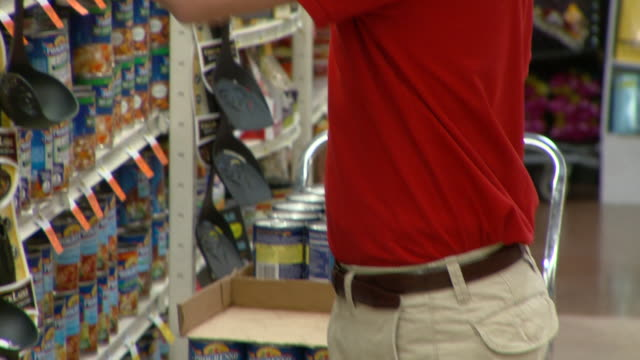 ms tu shop assistant stacking canned food on shelves in supermarket, richmond,  virginia, usa - 積み重ねる点の映像素材/bロール
