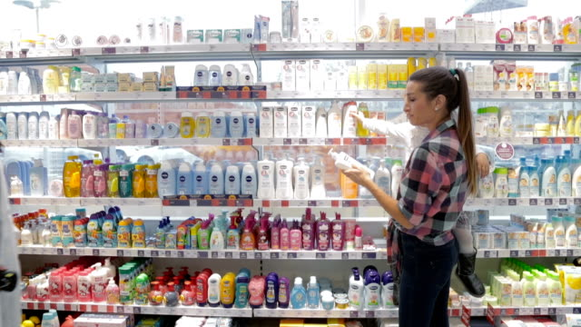 Shop assistant using bar code reader to help mother with child to choose hygiene product