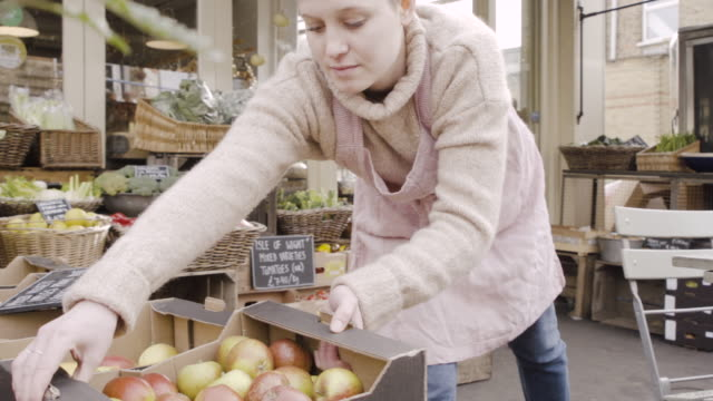 shop assistant walks with crate with organic apples and puts it down outside farm produce shop. - 帶 握住 個影片檔及 b 捲影像