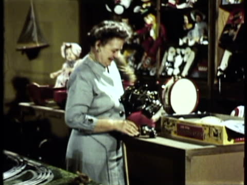 1953 ms zi cu shop clerk arranging toy trucks on display in toy store / usa - toy store stock videos and b-roll footage