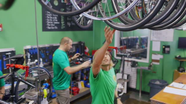 stockvideo's en b-roll-footage met shop employee grabs wheel and passes it to bike mechanic who attaches it to bicycle in busy repair shop - repareren