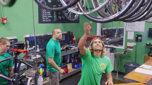 Shop employee picks out a bicycle wheel and hands off to mechanic in busy bike repair shop