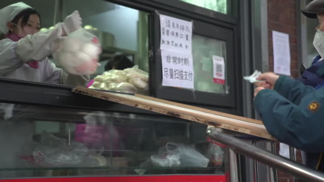 shop in beijing serving customers through hatch to keep a safe distance from them due to coronavirus - quarantine stock videos & royalty-free footage
