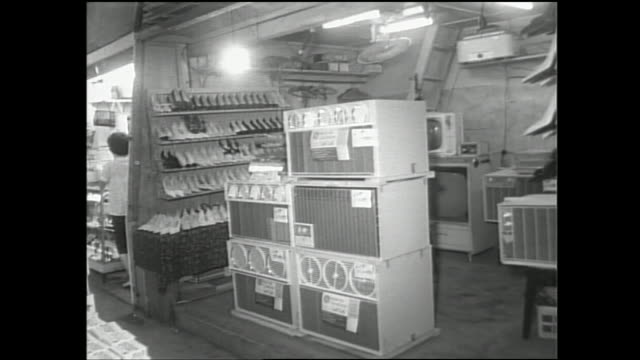 a shop in tokyo sells electrical appliances next to shoes. - 1960~1969年点の映像素材/bロール