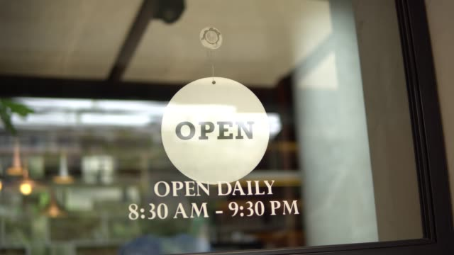 shop owner changing sign from closed to open and locking up - opening event stock videos & royalty-free footage