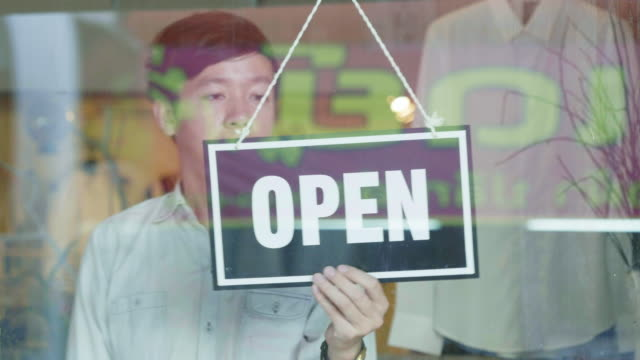 shop owner changing sign from closed to open - shop sign stock videos & royalty-free footage
