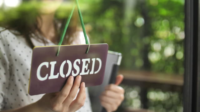 Shop owner changing sign from open to closed, Slow motion