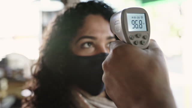 shop owner checking customer temperature in time of covid-19 - medical examination stock videos & royalty-free footage