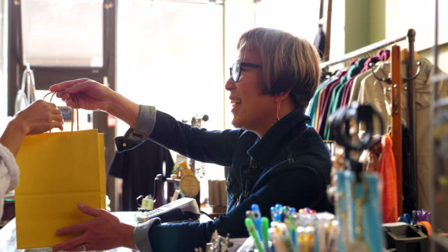 ms shop owner handing bag to client after shopping in clothing boutique - mid adult women stock videos & royalty-free footage