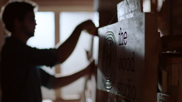 Shop owner hangs price tags on new skateboards by The Wood Studio sign