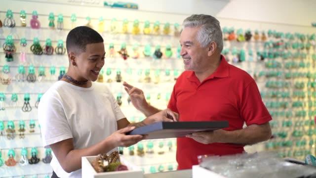 vidéos et rushes de propriétaire de magasin aidant le client choisissant une bague - satisfaction