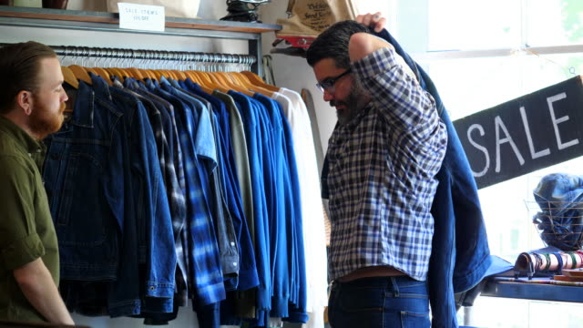 vídeos de stock, filmes e b-roll de ms shop owner helping customer try on denim jacket in mens boutique - jaqueta jeans