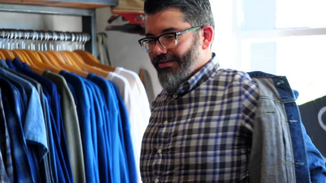 vídeos de stock, filmes e b-roll de ms pan td shop owner helping customer try on denim jacket in mens boutique - jaqueta jeans