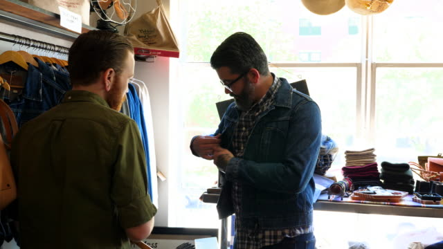 MS Shop owner helping customer try on denim jacket in mens boutique