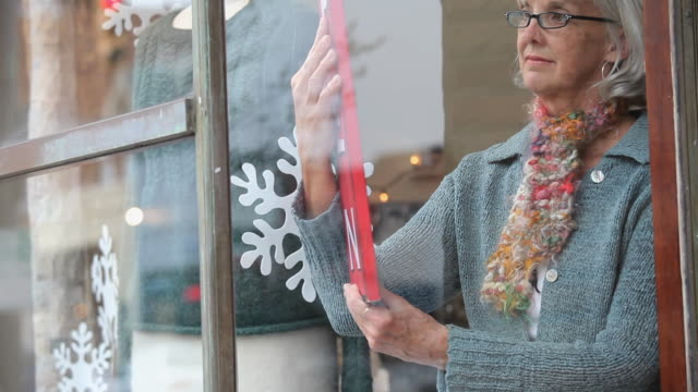 MS TU Shop owner placing open sign in window of knitting store / Richmond, Virginia, USA