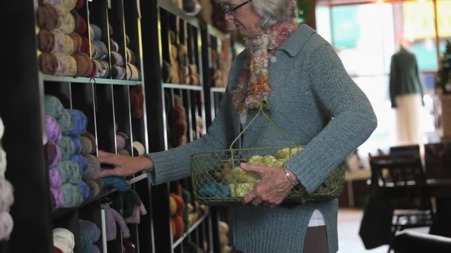 MS PAN Shop owner stacking shelves with yarn / Richmond, Virginia, USA