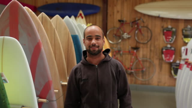vidéos et rushes de shop owner standing next to surfboards in sports store - entrepreneur