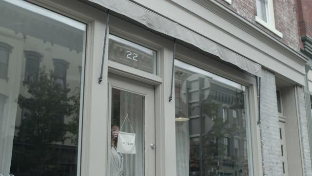vídeos y material grabado en eventos de stock de shop owner turns closing sign - lugar de comercio