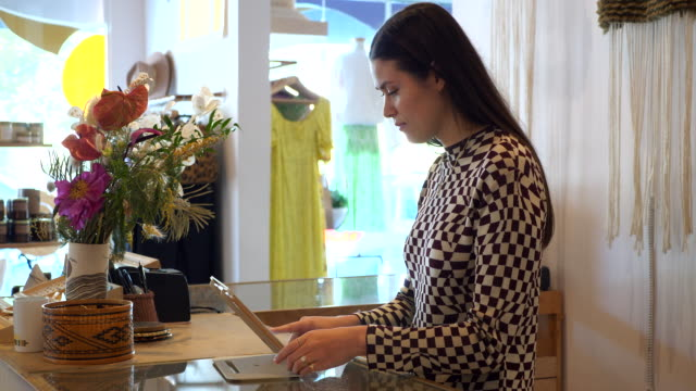 ms shop owner working on digital tablet behind counter in clothing boutique - clothes shop stock videos & royalty-free footage